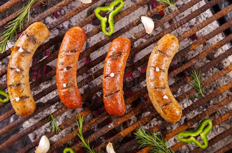 Top view of four grilling sausages on barbecue grill with some species. BBQ in the garden. Bavarian sausages.  stock photo