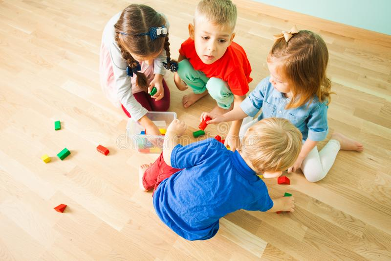 Top view kids cleaning a mess in children room. Top view of four preschoolers cleaning a mess of wooden toys in children room. Kids cooperating in house cleaning royalty free stock images