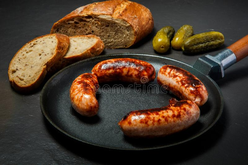 Top view four ruddy juicy sausages fried in large frying pan stock photography