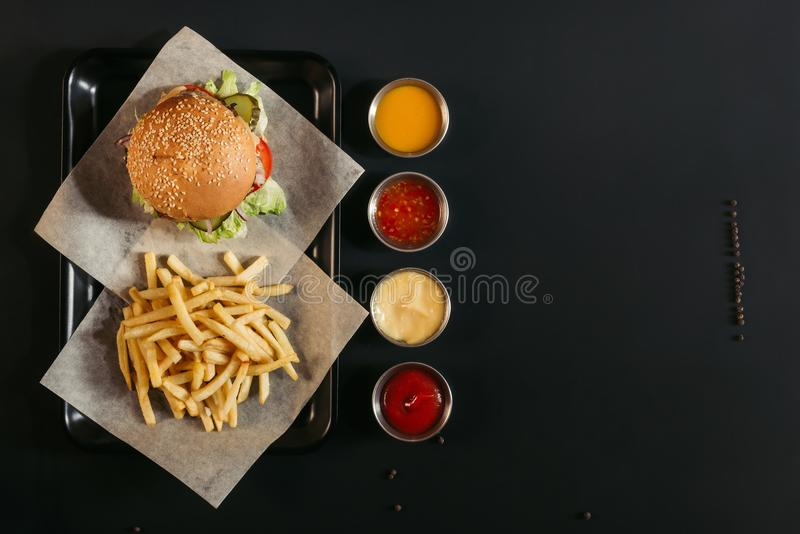 top view of french fries with delicious burger on tray and assorted sauces stock image
