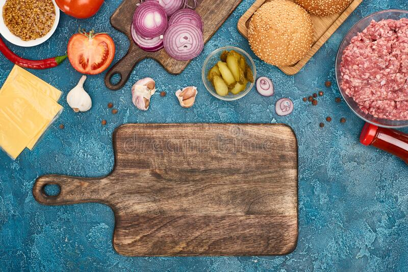 Top view of fresh burger ingredients near empty cutting board on blue textured surface. Stock image stock images
