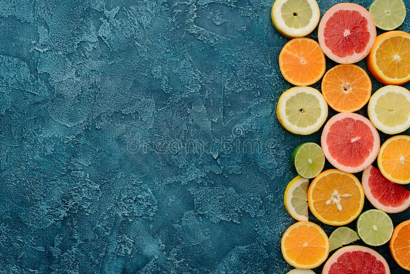 Top view of fresh citrus fruits slices on blue. Concrete surface stock photos