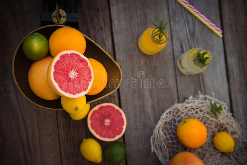 Top view Fresh citrus fruits in vintage scale and several oranges, lemons, grapefruit, lime and lemonade bottles on the old rustic royalty free stock photography