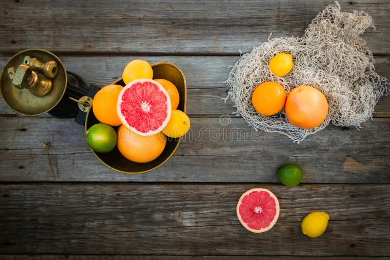 Top view Fresh citrus fruits in vintage scale and several oranges, lemons, grapefruit, lime on the old rustic wooden table with a royalty free stock photos