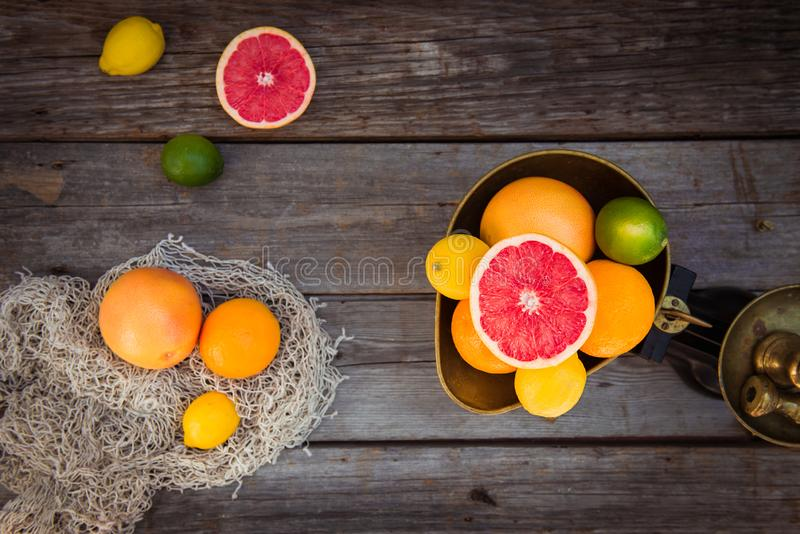 Top view Fresh citrus fruits in vintage scale and several oranges, lemons, grapefruit, lime on the old rustic wooden table with a royalty free stock images