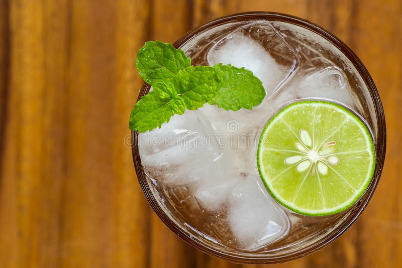 Top view of fresh cocktail with lime slice and mint on wood back stock photography