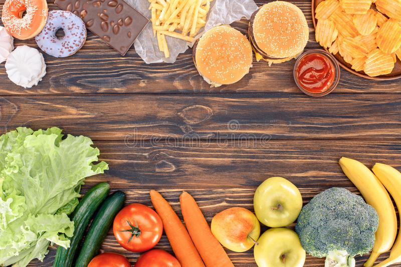 Top view of fresh fruits with vegetables and assorted unhealthy food on wooden table stock photo