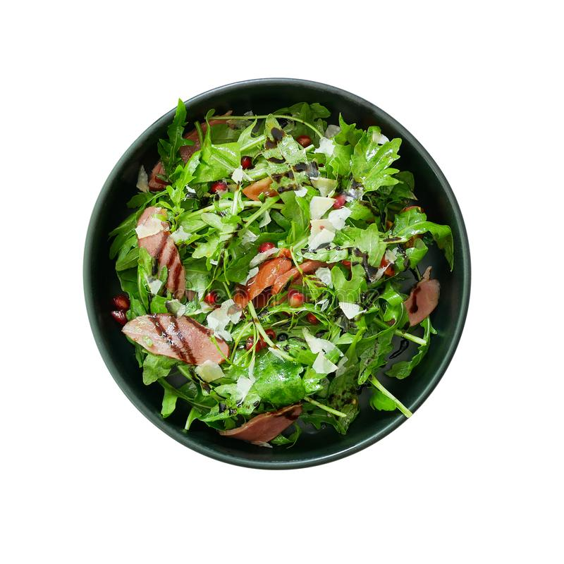 Top view of fresh green vegetable salad with sliced smoked duck and red pomegranate seeds and Parmesan cheese shaved in black bowl. Healthy food dish isolated royalty free stock photography