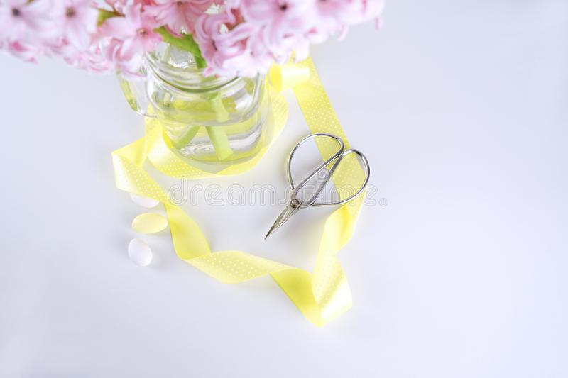 Top view of fresh hyacinth flower in vase with vintage scissors. And yellow ribbon on white with copy space. Concept for Mother`s day Easter and Women`s Day royalty free stock photo