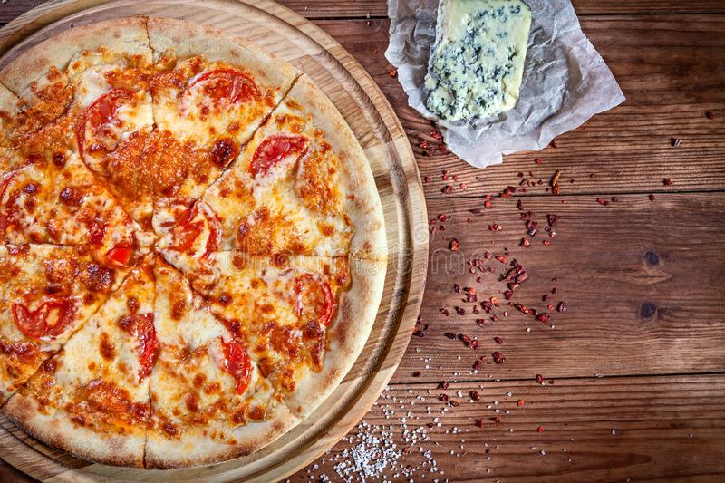 Top view on fresh italian pizza on wooden background with copy space for logo or design. View from above on margarita Pizza with stock photo