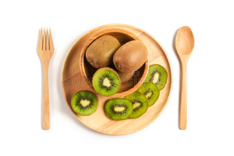 Top view Fresh Kiwi fruit sliced in wooden plate with wooden spoon and fork stock image