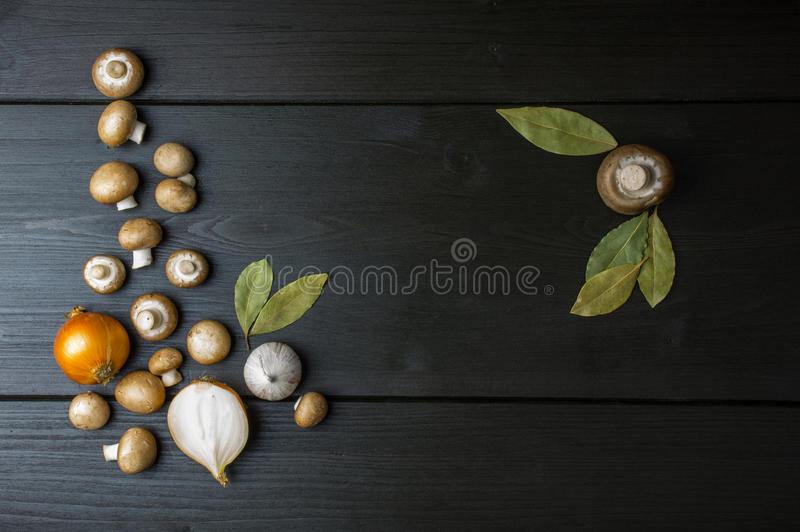 Top view of fresh mushrooms and onion with a bay leaf on dark wooden background. stock images