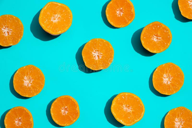 Top view fresh orange slices on bright blue background. . Copy Space. creative summer concept. Half of citrus in minimal stock photos