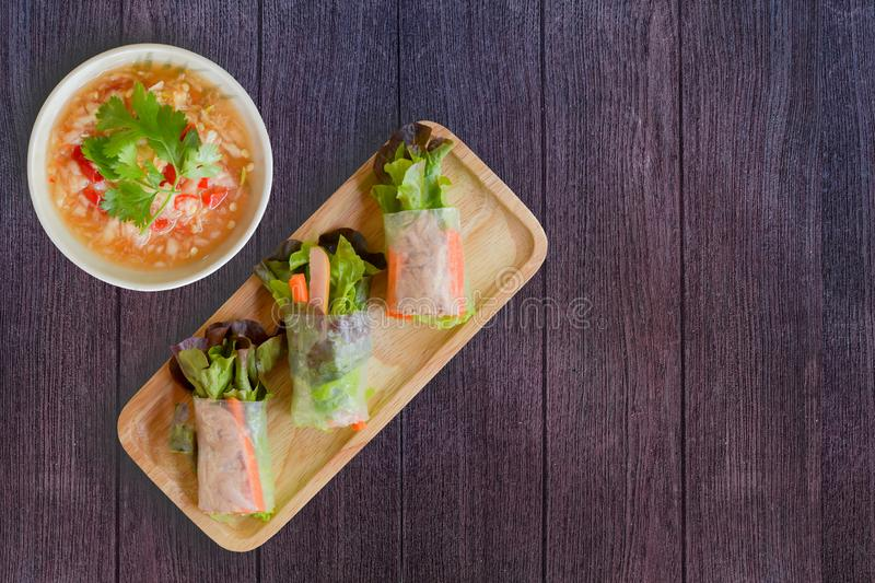 Top view fresh organic green vegetable lettuce and carrot slice rice wraps with tuna, sausage on wooden dish and Thai seafood stock photos