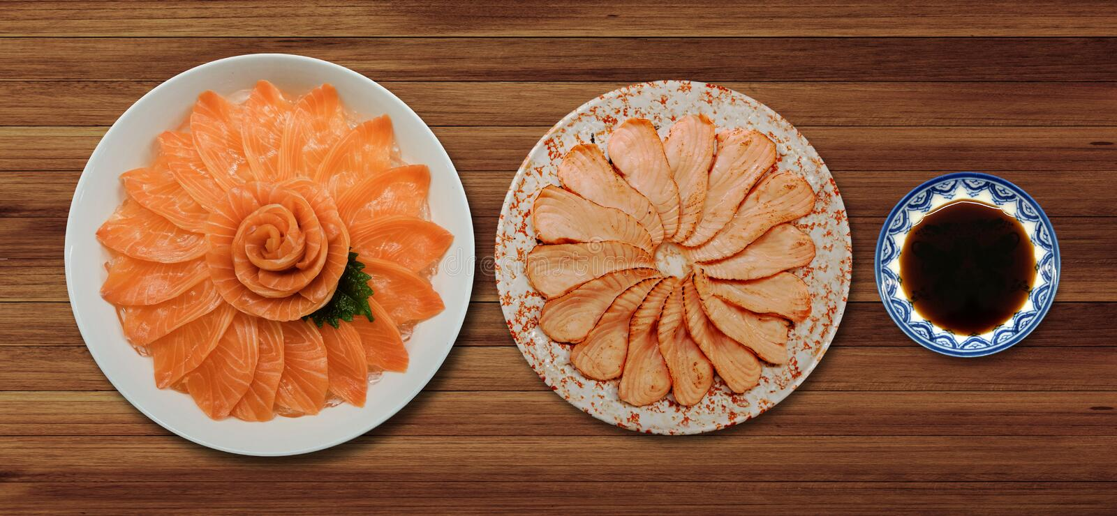Top view of fresh salmon and grill sashimi and shoyu serve on flower shape in white ice bowl boat isolated on wood background, Ja stock images