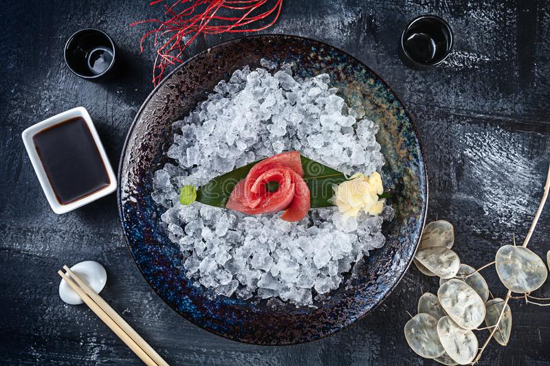 Top view on fresh sliced tuna sashimi served in bowl with ice on dark background. japanese food sashimi. Japan restaurant menu. stock photos