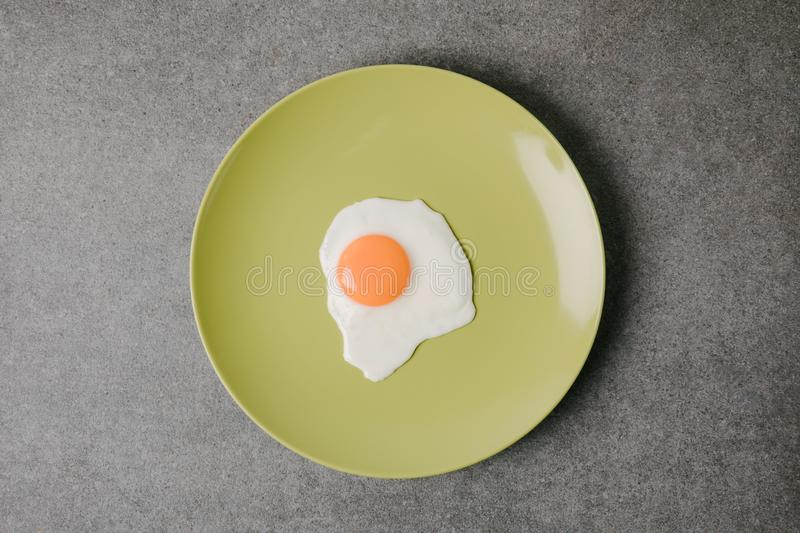 Top view of fresh tasty fried egg on plate on grey stock image