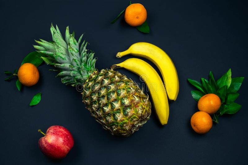 fresh tropical fruits layout pineapple,bananas, apple and tangerines on a black background stock images
