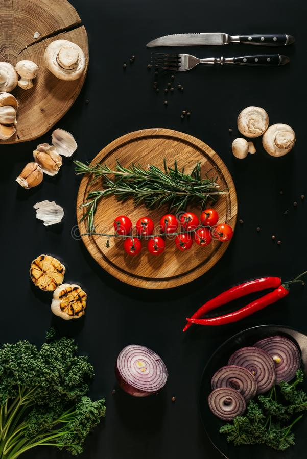 Top view of fresh vegetables and herbs, grilled garlic, fork with knife and wooden boards. On black stock image