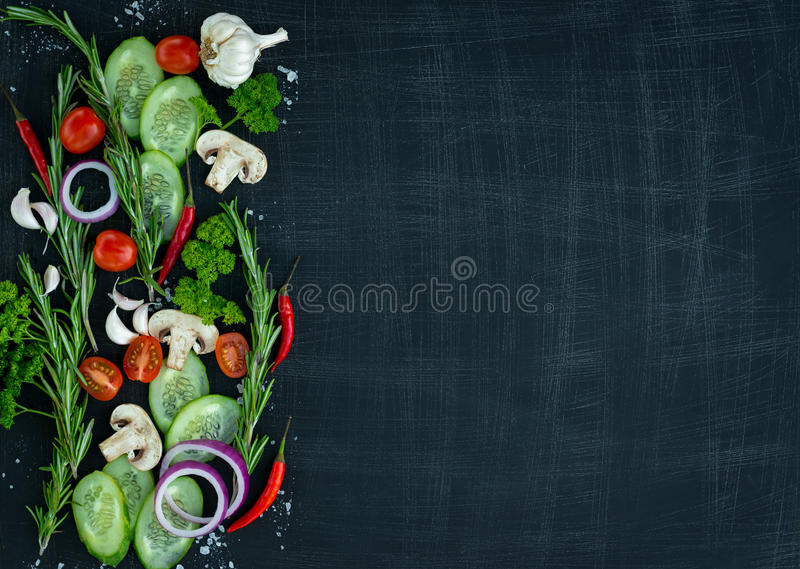 Top view of fresh vegetables and spices on dark wooden background with space for text. Vegetarian food, health or cooking royalty free stock photo