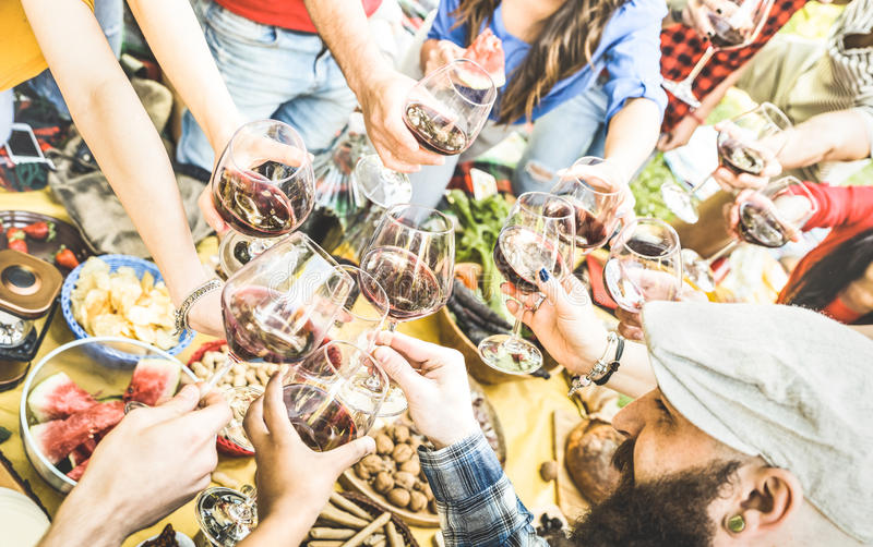 Top view of friend hands toasting red wine glass at barbecue. Top view of friend hands toasting red wine glass and having fun outdoor cheering at picnic stock photos