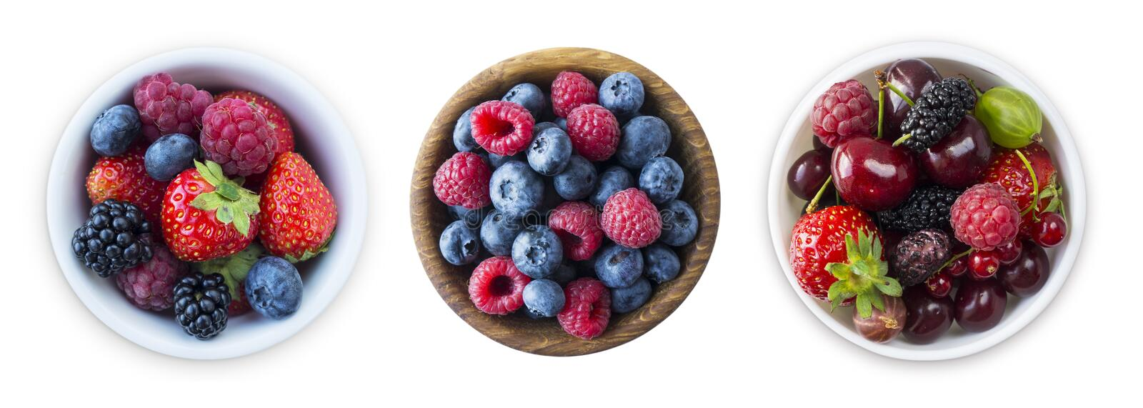 Top view. Fruits and berries in bowl isolated on white background. Ripe raspberries, blueberries, cherries, strawberries, blackber royalty free stock photos