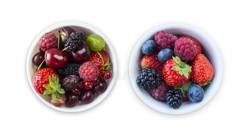 Top view. Fruits and berries in bowl isolated on white background. Ripe raspberries, cherries, strawberries, blackberries and blue stock images
