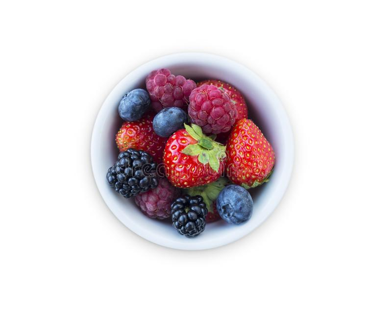Top view. Fruits and berries in bowl isolated on white background. Ripe raspberries, strawberries, blackberries and blueberries. B stock photo