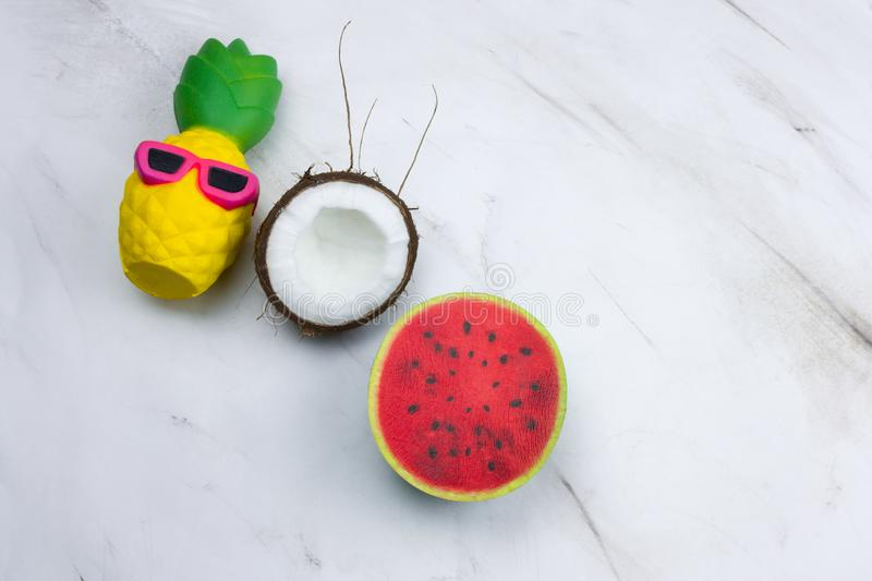 funny pineapple toy in sunglasses,watermelon and coconut on a marble table stock image