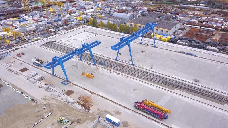Top view of the gantry crane on the transport site. Clip. Various brands and colours of Shipping containers stacked by. Transtainers Mobile gantry cranes off of stock photo