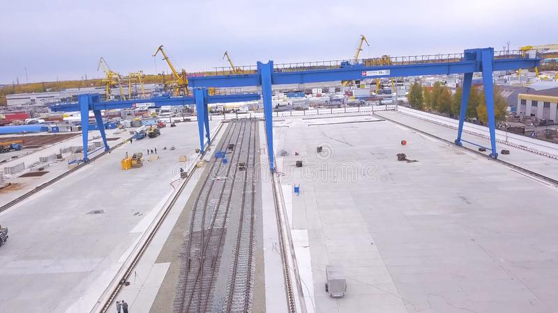 Top view of the gantry crane on the transport site. Clip. Various brands and colours of Shipping containers stacked by. Transtainers Mobile gantry cranes off of stock photography