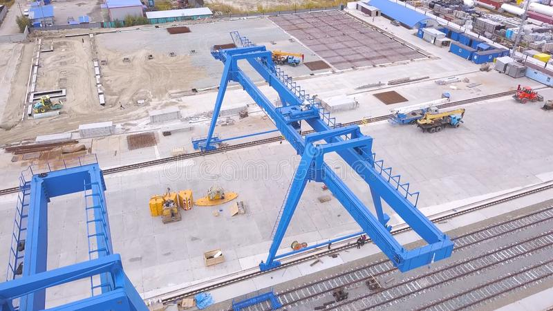 Top view of the gantry crane on the transport site. Clip. Various brands and colours of Shipping containers stacked by. Transtainers Mobile gantry cranes off of royalty free stock image