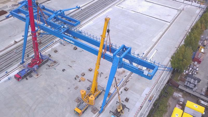 Top view of the gantry crane on the transport site. Clip. Various brands and colours of Shipping containers stacked by. Transtainers Mobile gantry cranes off of royalty free stock photos