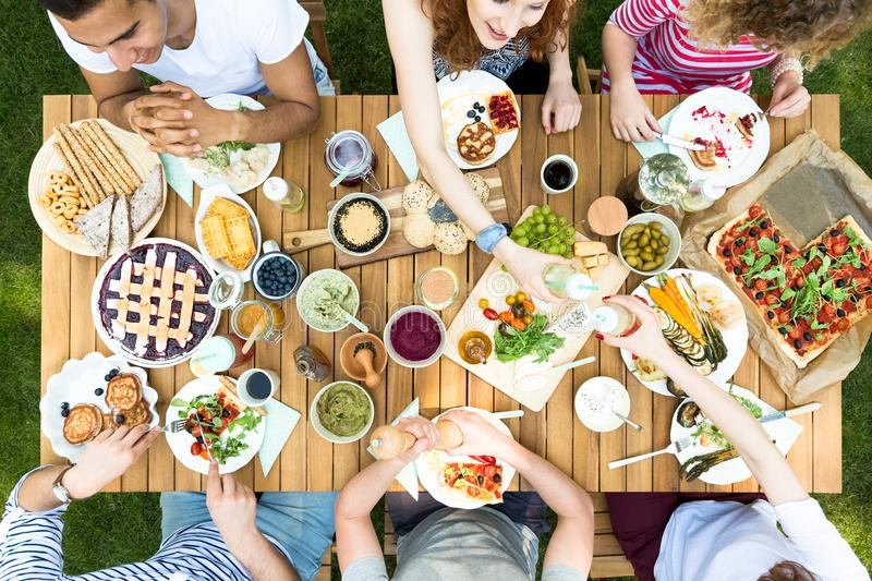 Top view on garden table with pastry, fruits and pizza during me royalty free stock photography