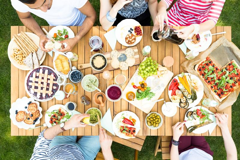 Top view on garden table with salad, fruits and pizza during out stock images