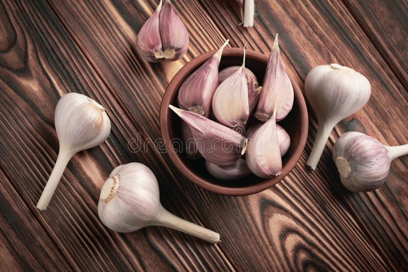 Top view garlic cloves in a ceramic bowl on a wooden table stock photo