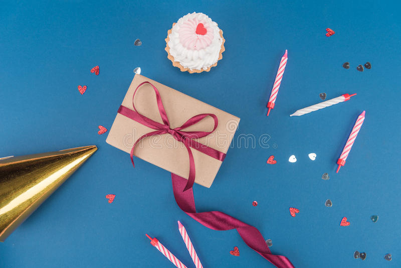 Top view of gift box, cake, candles and birthday hat isolated on blue. Birthday party concept stock image
