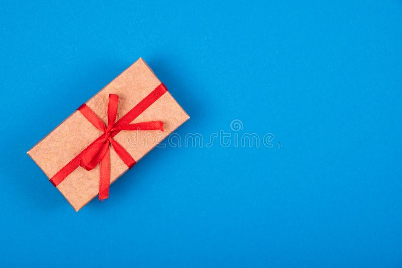 Gift box with red ribbon and bow on cyan blue background. Top view of gift box with red ribbon and bow on cyan blue background. Minimalism concept. Greetings royalty free stock photos