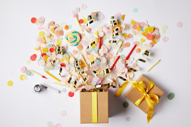 Top view of gift box and scattered confetti pieces on white surface royalty free stock photos
