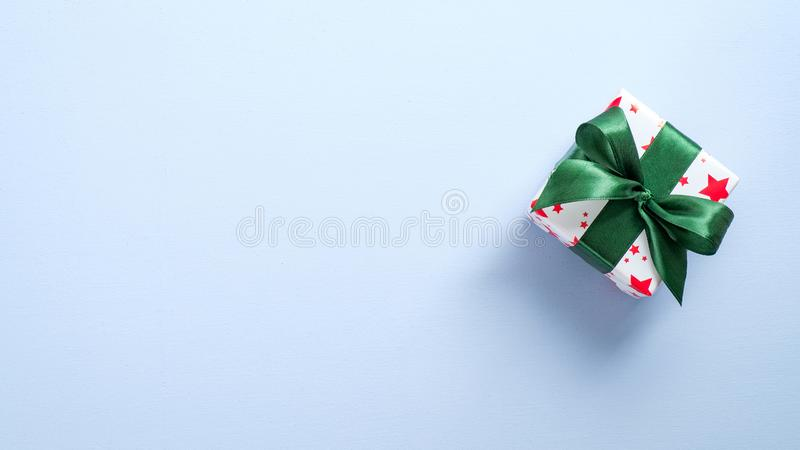 Top view gift box wrapped festive paper with green ribbon bow. Flat lay Christmas holiday present on pastel blue background with stock photos