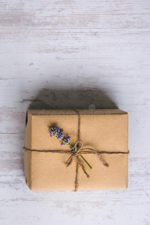 Top view of a gift box wrapped in kraft paper decorated with lavender flower over white wood rustic background. Copy space. royalty free stock image