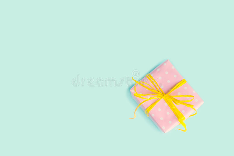 Top view of a gift box wrapped in pink dotted paper and tied yellow bow over light blue background. Vintage effect. royalty free stock images