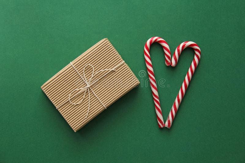 Top view. Gift Kraft Brown Color Box and Candy Canes Red and White in Heart Shape Lies on the Green Background, View From the Top. Gift Kraft Brown Color Box and royalty free stock photos