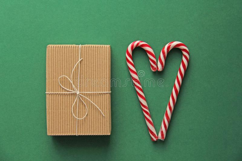 Top view. Gift Kraft Brown Color Box and Candy Canes Red and White in Heart Shape Lies on the Green Background, View From the Top. Gift Kraft Brown Color Box and royalty free stock image