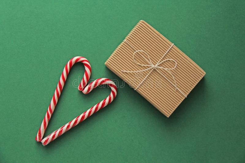 Top view. Gift Kraft Brown Color Box and Candy Canes Red and White in Heart Shape Lies on the Green Background, View From the Top. Gift Kraft Brown Color Box and royalty free stock photo