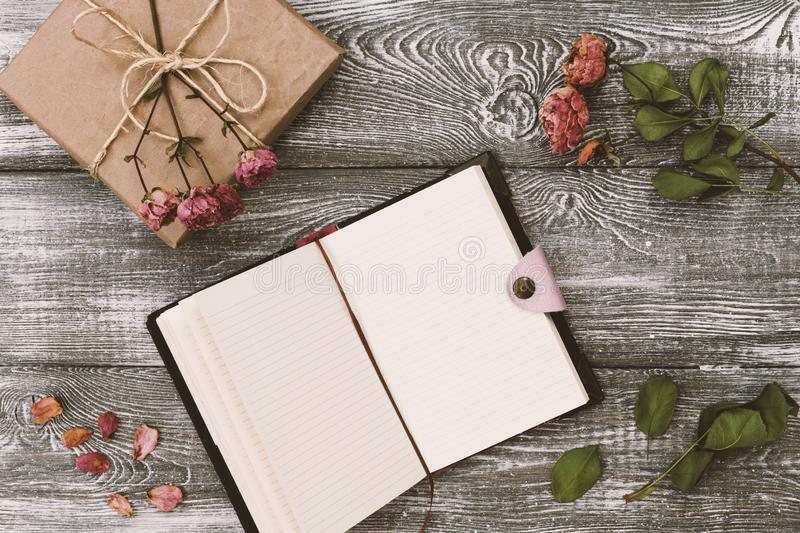 Top view of a gift wrapped in craft paper and a diary or notebook and dried rose flower on a gray wooden table. Flat design. Copy stock photography