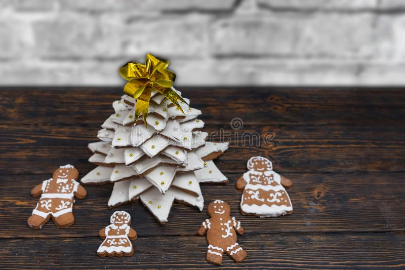 Top view of gingerbread Christmas tree with cute gingerbread family on wooden desk near snow-covered brick wall. Mockup for seasonal offers and holiday post royalty free stock photography