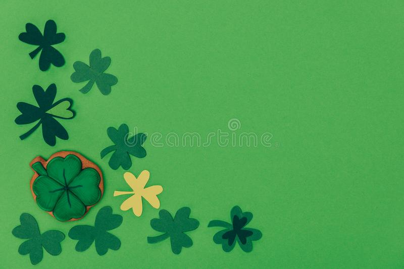Top view of gingerbread in shape of shamrock and paper shamrock isolated on green, st patricks day concept stock photo