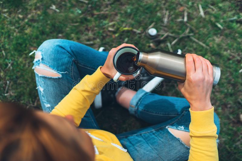 Top view girl holding in hands cup of hot tea on green grass in outdoors nature park, beautiful woman hipster enjoy drinking cup royalty free stock images
