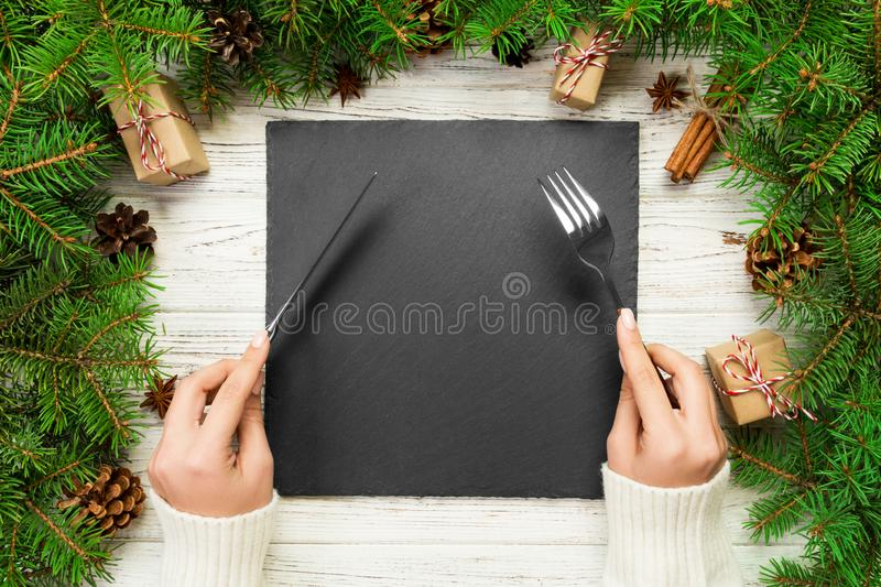Top view girl holds fork and knife in hand and is ready to eat. Empty black slate square plate on wooden christmas background. Holiday dinner dish concept with royalty free stock images